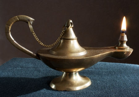 old brass magic lamp burning on the table Standard-Bild