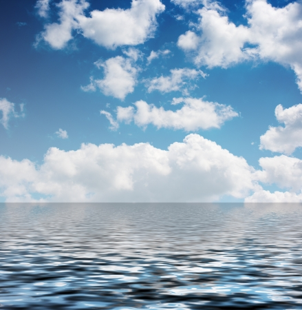 white clouds in the blue sky reflected in the water on summer day photo