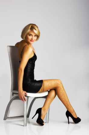 young beautiful woman in black dress sitting on a chair in studio photo