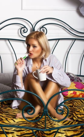 young beautiful woman brushing her teeth in bed photo