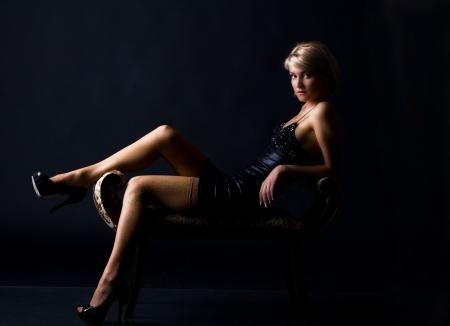 young woman in a black dress posing lying Standard-Bild