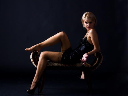 young woman in a black dress posing sitting on dark background photo
