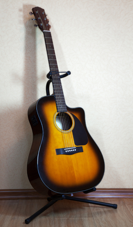 six-string acoustic guitar on a stand on light background photo