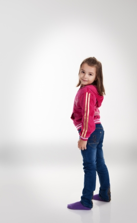 little girl in blue jeans and a red jacket posing standing in the studio photo