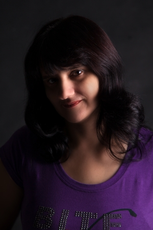portrait of a beautiful young woman in a blue blouse on a dark background