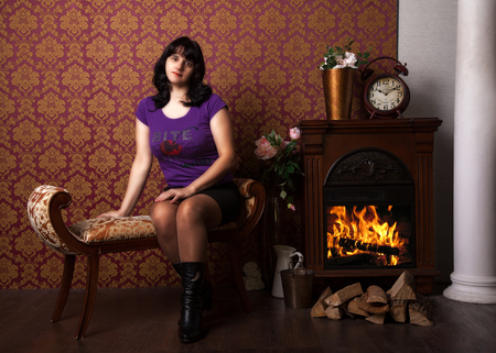 banquette: young beautiful woman in a blue shirt black skirt and boots sitting on a banquette near the fireplace Stock Photo