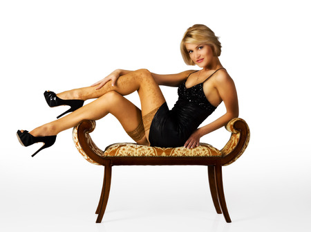 young beautiful woman in black dress posing sitting on a chair in the studio