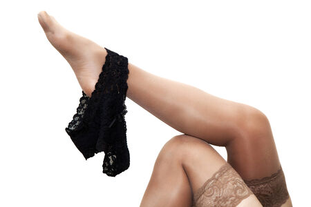 black panties hanging on a female leg in stocking isolated on white background