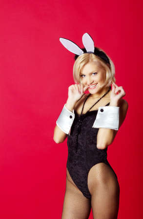 young beautiful woman in rabbit costume on red  photo