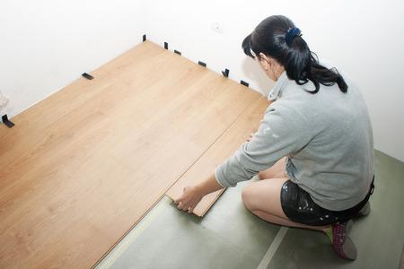 young beautiful woman puts laminate flooring