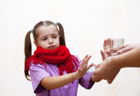 little sick girl refuses to take the medicine from her mother Standard-Bild