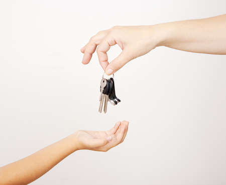 mother gives the keys to a little daughterl at home hands closeup