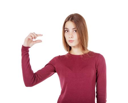 少しのジェスチャーを示す赤いセーターの美しい少女 写真素材