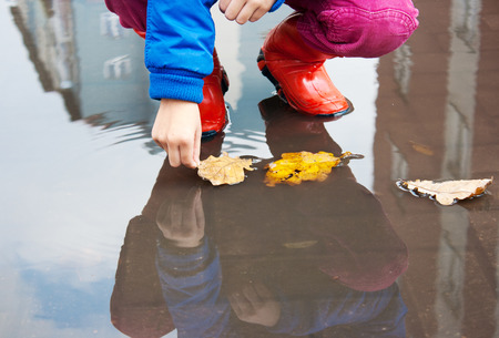 little girl in red rubber boots holding yellow leaf in a puddle closeup photo