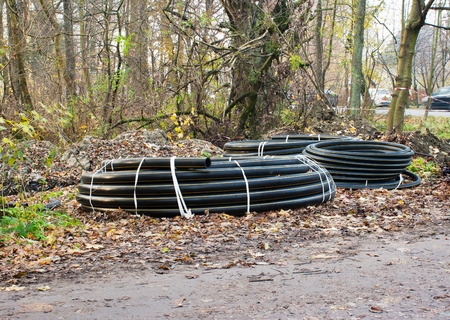 three scrolls of plastic sewer pipe prepared for repair outside Stock Photo
