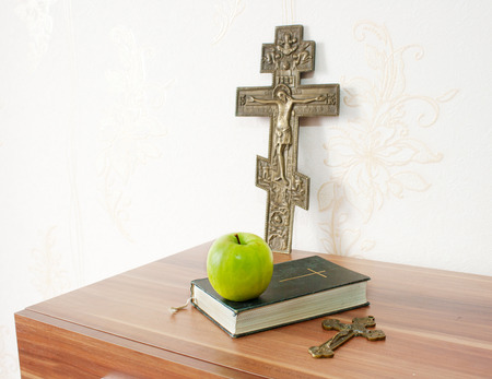 holy bible with green apple and two crosses on the brown wooden table Stock Photo