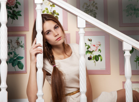 young beautiful girl in light dress sits on the stairs indoor Stock Photo
