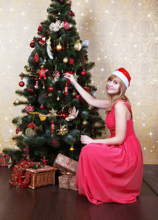 young beautiful girl in Santa hat and pink dress sitting near Christmas tree photo