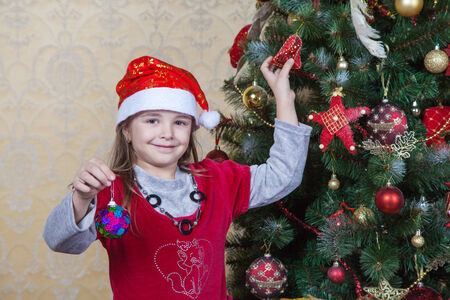 little girl in Santa hat and red dress near Christmas tree