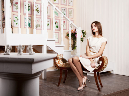 young beautiful girl in a bright dress sitting on a chair Stock Photo