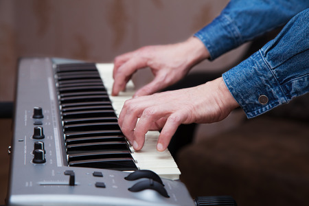 keyboard instrument: hands of the musician on the keyboard synthesizer