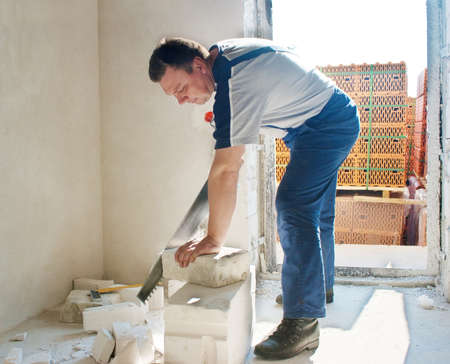 middle-aged man worker in blue trousers and gray t-shirt saws silicate brick in the room of new house photo