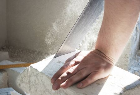 workers hand sawing silicate brick close-up in the room photo