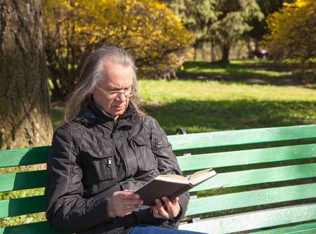 haired elderly man in a black jacket and glasses reading a book sitting on a bench in city park on sunny spring day