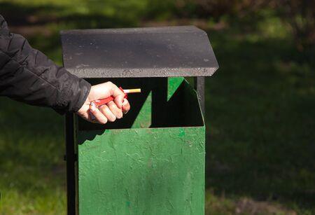 breaks: male hand breaks a pack of cigarettes near a waste bin outside Stock Photo
