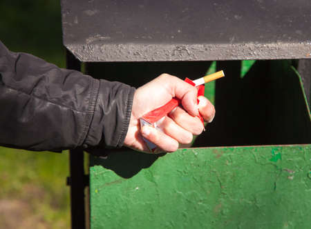 breaks: mans hand breaks a pack of cigarettes about a waste bin closeup outside Stock Photo