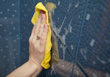 sterilize: female hand washes the blue tile on the wall with a yellow cloth lather in the bathroom closeup