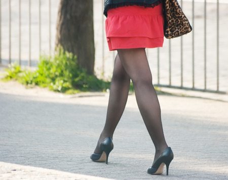 black stockings: woman in a red skirt, black stockings and shoes walking on the sidewalk Stock Photo