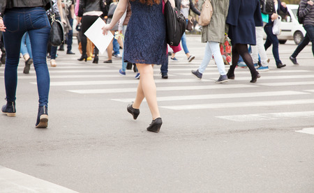 line of people: legs of pedestrians on a pedestrian crossing on spring day