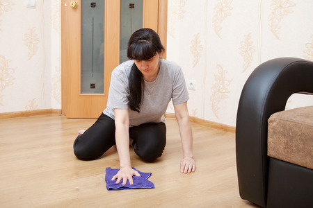 floor cloth: young brunette woman in a gray T-shirt and black trousers washes wooden floor with blue cloth