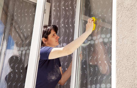 window panes: young woman in blue shirt washes a window pane
