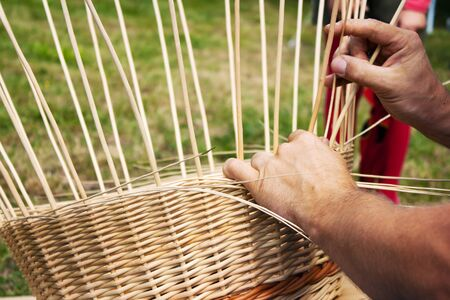 hands of man braiding wicker basket