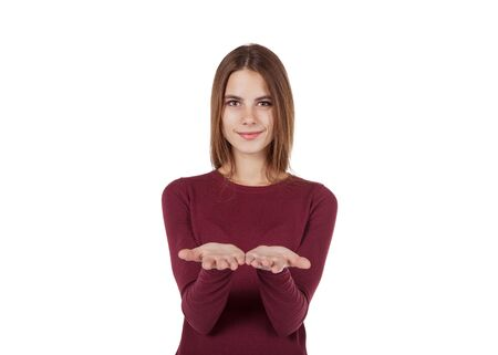 smiling girl in red sweater offers something on the palms Stock Photo