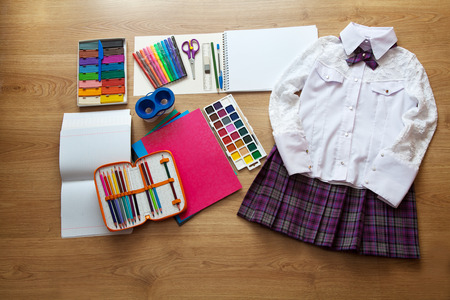 watercolor pen: set of school supplies. red skirt, white blouse, pen, pencil, clored paper, copybook, watercolor paint on the floor Stock Photo