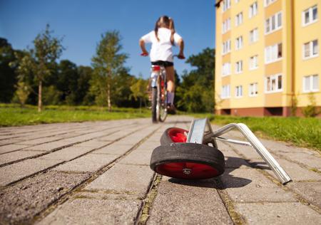bicicleta: ruedas adicionales de la moto tumbada en la carretera. ni�a monta una bicicleta de distancia Foto de archivo