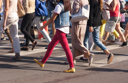 foot step: feet of young pedestrians walking on the crosswalk on summer day