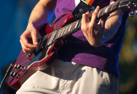 hands of guitarist in concert outside on summer closeup Stock Photo