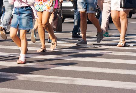 feet of the pedestrians crossing on city street closeup Stock Photo