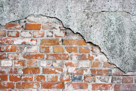 old crumbling brick wall with cracked plaster Stock Photo