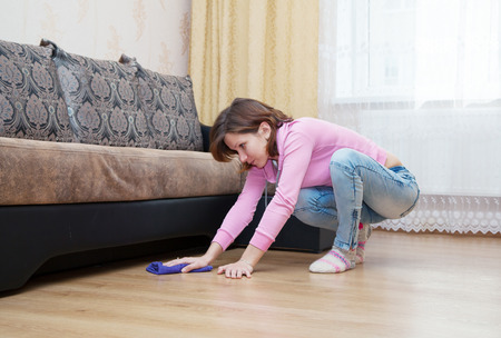 young brunette woman in a pink blouse and blue jeans washing wooden floor with blue floorcloth Banque d'images