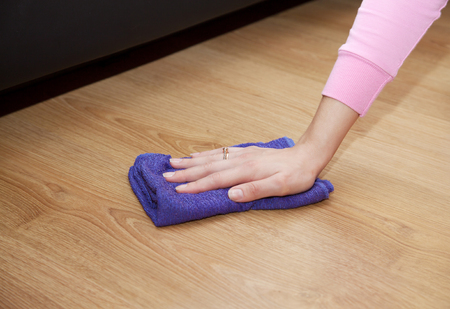 woman's hand cleaning the wooden floor with a blue floorcloth closeup