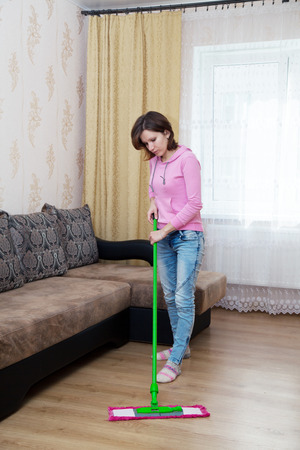 young woman in a pink blouse and blue jeans washing wooden floor with a mop