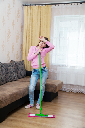 young tired woman in a pink blouse and blue jeans washing wooden floor with a mop