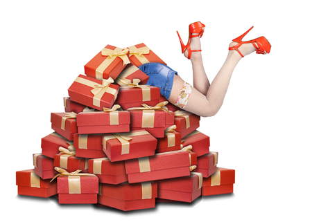 cajas navideñas: womans legs sticking out from a pile of gift boxes