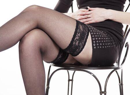 mujeres sentadas: piernas de la mujer sentada en medias negras Primer
