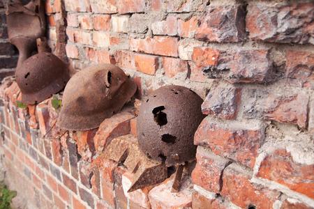 holed: three old rusty military helmets near the brick wall